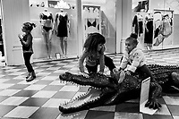 Switzerland. Ticino. Mendrisio. A group of young girls play with a fake crocodile inside the Foxtown. FoxTown is a huge outlet commercial center where customers come to shop. 6.11.2016  © 2016 Didier Ruef