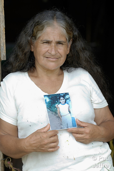 Maria Brigida Gonzalez, a member of the peace community of San Jose de Apartado, Colombia.  In 1997, 1400 war-weary peasants declared they would no longer cooperate with any of the armed parties in the hemisphere's longest-running war. They paid a heavy price for their witness; more than 200 members of the community have been killed. In 2013, two army generals were indicted for a 2005 massacre in the community, and on December 10, 2013, Colombian President Juan Manuel Santos Calderon, in the name of the state, publicly asked the community for forgiveness. In this image, Gonzalez holds a photo of her daughter Elisenia, killed by the army in 2005.
