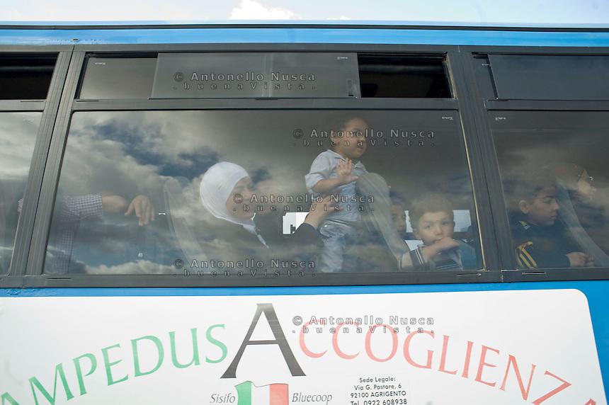 Profughi siriani lasciano l'isola di Lampedusa per raggiungere i centri di accoglienza in Sicilia.