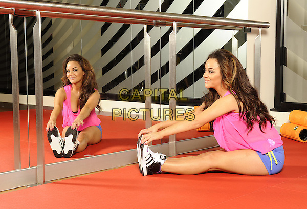 Chelsee Healey.Photoshoot with Chelsee Healey in training ahead of her Virgin Active Triathlon on 22nd September, Virgin Active Health Club, London, England..September 10th, 2012.exercise full length pink top workout blue shorts  mirror reflection side profile warm up cool down stretch stretching sitting.CAP/FIN.©Steve Finn/Capital Pictures.