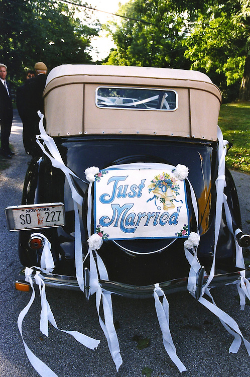 Antique car with Just Married sign affixed to the trunk.