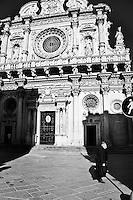Donna anziana passa davanti alla Basilica di Santa Croce.