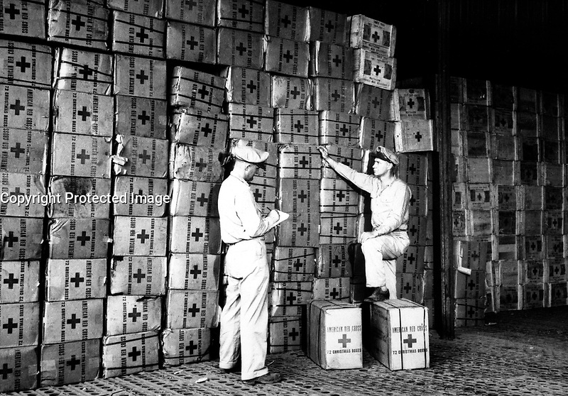 Red Cross field men preparing to ship gift boxes to servicemen fighting on Leyte and other islands in the Philippines.  Efforts are being made to assure each man a gift package on Christmas Day.  New Guinea, November 20, 1944.  American Red Cross.  (OWI)<br /> NARA FILE #:  208-AA-324A-1<br /> WAR &amp; CONFLICT BOOK #:  850