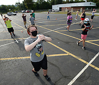 Dillon Wiggins (center), a sophomore at Greenland High School, marches Tuesday, July 28, 2020, as Jessica Osorto (right), band director, leads practice for the Greenland Pirate Band in the Greenland Elementary School parking lot. The band was learning how to march backwards while still being able to start and stop in formation. Visit nwaonline.com/200729Daily/ for today's photo gallery.<br /> (NWA Democrat-Gazette/Andy Shupe)
