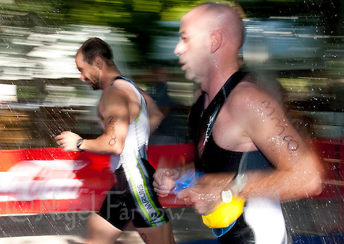 30 MAY 2009 - MADRID,ESP - Competitors run through the showers at the swimexit - Spanish Triathlon Championships .(PHOTO (C) NIGEL FARROW)