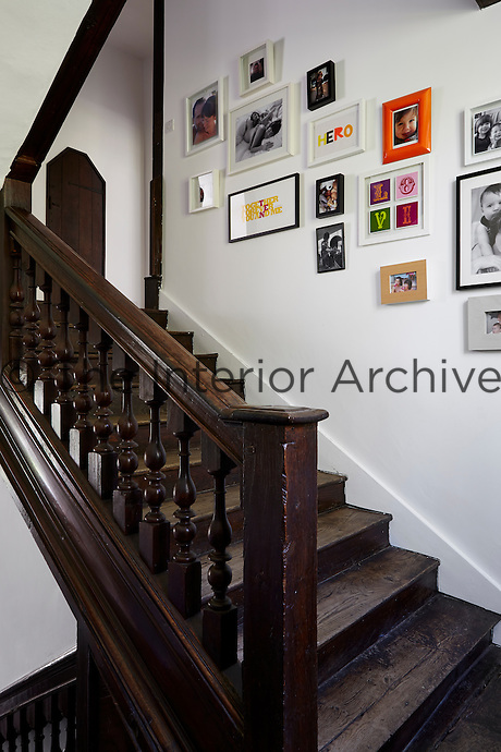 A wooden staircase, lined by picture frames, leads to a small landing.