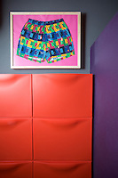 "In the bathroom ""Pop Short"", a work by the Milanese artist Pab, hangs above a bright-red shoe cupboard"