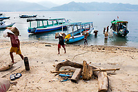 Men unload bags of concrete mix on the tiny Island of Gili Air, Indonesia. Most suppplies have to be shipped in from off-island.