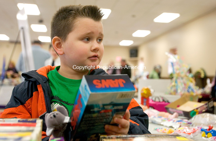 BETHLEHEM CT. 05 April 2014-040514SV07-Ryan Johnstone, 7, of Oakville sets up a VHS video he was selling at an indoor flea market sponsored by the Bethlehem Grange at Memorial Hall in Bethlehem Saturday. Proceeds from the event go toward the support of Grange community service projects.<br /> Steven Valenti Republican-American