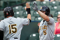 Salt Lake Bees outfielder Scott Cousins (5) greets teammate Matt Long after he scored during the Pacific Coast League baseball game against the Round Rock Express on August 10, 2013 at the Dell Diamond in Round Rock, Texas. Round Rock defeated Salt Lake 9-6. (Andrew Woolley/Four Seam Images)