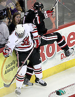 A collision between UNO's Alex Hudson and St. Cloud State's Kevin Gravel catches the attention of a couple fans. UNO beat St. Cloud State 3-0 Friday night at Qwest Center Omaha.  (Photo by Michelle Bishop)