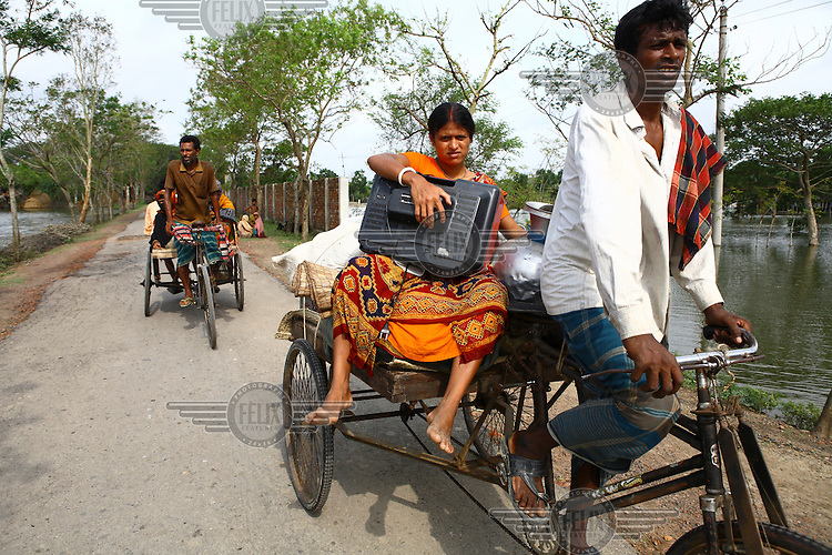 A woman displaced by Cyclone Aila carries her TV and other belongings on a rickshaw. Thousands of people were displaced in Shyamnagar Upazila, Satkhira district after Cyclone Aila struck Bangladesh on 25/05/2009, triggering tidal surges and floods..