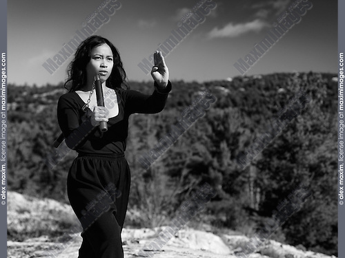 Dramatic black and white portrait of a young asian woman martial artis practicing nunchaku in the nature. Ontario, Canada.