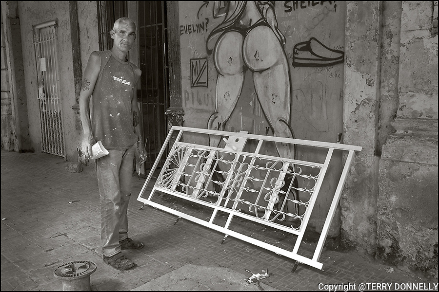Havana, Cuba:<br /> Man painting gate on the street
