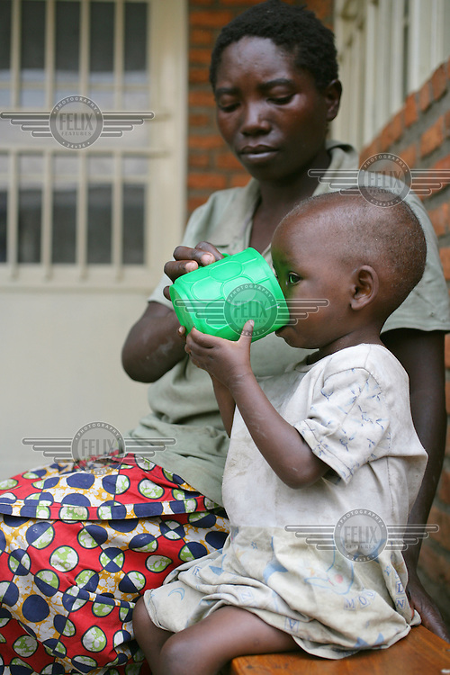A child receiving a food supplement at a health clinic.