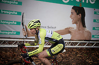 an elite women's racer (Rozanne Slik?) with blooded eye passing in front of the contrasting title sponsor's billboard<br /> <br /> Superprestige Gavere 2014