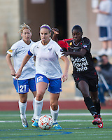 Boston Breakers midfielder Leslie Osborne (12) with FC Indiana midfielder Manoucheka Pierre Louis (20) closing in for a tackle.  The Boston Breakers beat FC Indiana 4-1 in their home opener at Dilboy Stadium.