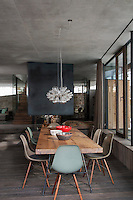 Vintage Eames chairs surround a rustic wooden table in the open plan dining area