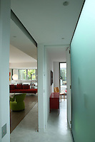 Walls of both transparent and frosted glass are used in the corridor between a bedroom and the living area