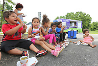 NWA Democrat-Gazette/DAVID GOTTSCHALK Egypt Goings (left), 4, enjoys lunch Monday, June 3, 2019, with neighborhood children provided by the Fayetteville Public Schools' Purple Dog Food Truck at the Shelton Tucker Craft American Legion Post 27 on Curtis Avenue in Fayetteville. The American Legion location is the new third location for the food truck that will provide a lunch to those 18 years and younger. Local school districts begin their free summer food service programs for kids this week.