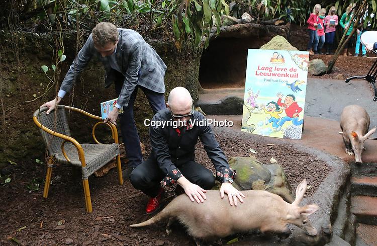 """Foto: VidiPhoto..ARNHEM - Kinderboekenschrijver Paul van Loon heeft dinsdag tussen de aardvarkens van Burgers' Zoo zijn nieuwste boek """"Lange leve de Leeuwenkuil!"""" gepresenteerd. Het eerste exemplaar werd overhandig aan dierentuindirecteur Alex van Hooff (l). De boeken van Van Loon zijn geïnspireerd op de jeugd van Van Hooff. Na het officiële gedeelte mochten kinderen hun boek laten signeren door de populaire schrijver. Dierentuindirecteur Alex van Hooff van het jubilerende Burgers' Zoo groeide als kind samen met zijn twee zussen op met een dierentuin als achtertuin. Deze avontuurlijke verhalen hebben Paul van Loon geïnspireerd om een verhalenreeks te schrijven over de kinderen Daniël en Suzina Durvers die opgroeien in Durvers' Zoo en vanuit hun boomhut  allerlei spannende avonturen beleven.."""