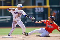 Florida Gators shortstop Richie Martin (12) turns a double play against the Virginia Cavaliers in Game 11 of the NCAA College World Series on June 19, 2015 at TD Ameritrade Park in Omaha, Nebraska. The Gators defeated Virginia 10-5. (Andrew Woolley/Four Seam Images)