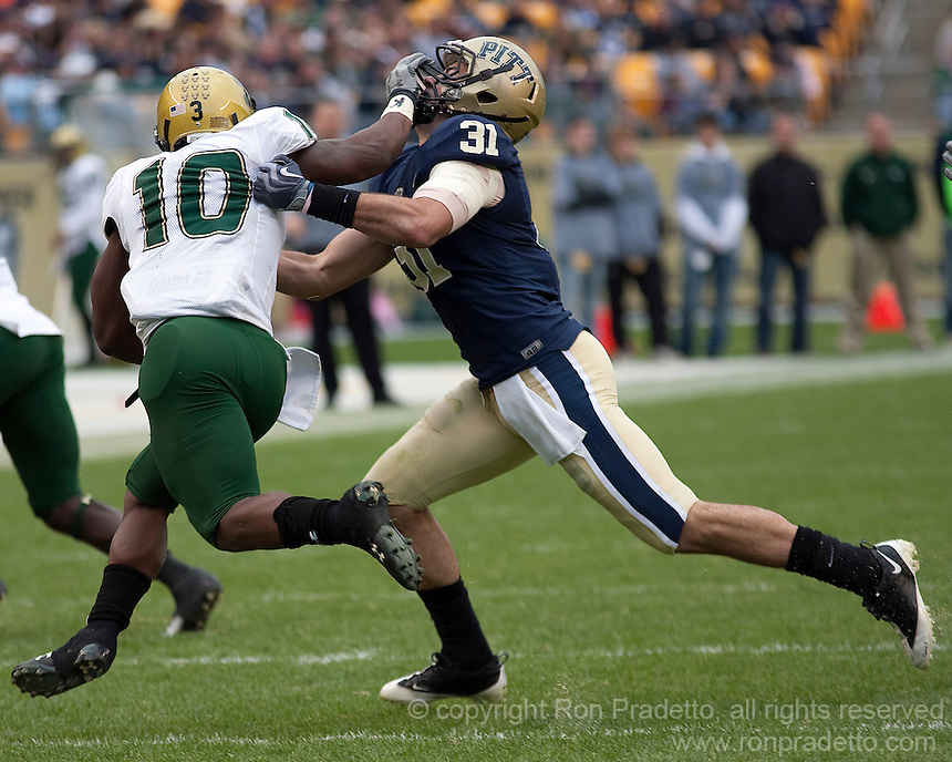 Pittsburgh defensive back Dom DeCicco (31) gets a stiff arm from South Florida's running back Moise Plancher (10). The Pittsburgh Panthers defeated the South Florida Bulls 41-14 at Heinz Field, Pittsburgh, PA on October 24, 2009.