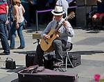 Male busker playing guitar in Abbey churchyard, Bath, Somerset, England
