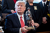 U.S. President Donald Trump holds up a statue he received as a gift while meeting with county sheriffs in the Oval Office of the White House in Washington, D.C., U.S., on Tuesday, Feb. 7, 2017. The Trump administration will return to court Tuesday to argue it has broad authority over national security and to demand reinstatement of a travel ban on seven Muslim-majority countries that stranded refugees, triggered protests and handed the young government its first crucial test. <br /> Credit: Andrew Harrer / Pool via CNP
