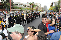 Phoenix, Arizona. April 25, 2012 - Phoenix Police officers line up along a section of northbound Central Avenue as demonstrators block the street in protest. Police made a formation to push back protesters toward the sidewalk.  About 500 people protested the controversial SB 1070 law on the same day U.S. Supreme Court justices heard legal arguments on the Arizona vs. United States case. At the end of the march, six activists blocked Central Avenue by sitting in the middle of the street. They all were arrested by the Phoenix Police Department and taken to the Fourth Avenue County Jail. Photo by Eduardo Barraza © 2012