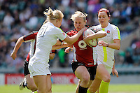 Mandy Marchak of Canada breaks through the tackle of Michaela Staniford of England (left) as Joanne Watmore of England looks on during the iRB Challenge Cup at Twickenham on Sunday 13th May 2012 (Photo by Rob Munro)