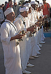 Male musicians wearing white traditional robes dance with drums, Essaouira, Morocco