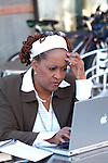 African American woman working on laptop, looking troubled