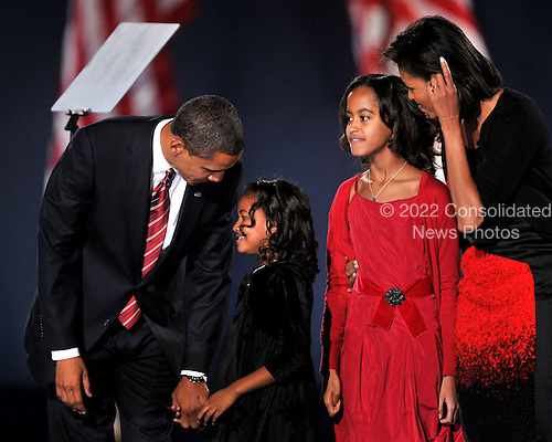 Chicago, IL - November 4, 2008 -- United States President-elect Barak Obama shares a thought with his daughter, Sasha, prior to speaking in Lower Hutchinson Field, Grant Park, Chicago, Illinois after his election as President of the United States on Tuesday, November 4, 2008.  From left to right: President-elect Obama; Sasha Obama; Malia Obama; and Michelle Obama..Credit: Ron Sachs / CNP.(Restriction: No New York Metro or other Newspapers within a 75 mile radius of New York City)