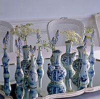 A collection of blue and white Chinese porcelain vases on a mirrored tray each hold a flower