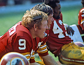 Washington Redskins quarterback Sonny Jurgensen (9), left, speaks to coaches in the press box as he sits on the bench with teammates Billy Kilmer (17), center,  and Larry Brown (43), right, during a game against the San Diego Chargers at RFK Stadium in Washington, D.C. on August 25, 1973.  The Redskins won the game 38 - 0..Credit: Arnie Sachs / CNP