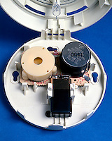 IONIZING SMOKE DETECTOR<br /> Radioactive Source Ionizes Charged Air Particles<br /> (close-up) A radioactive source ionizes charged air particles between two electrodes. When smoke particles enter the chamber they attract the ions and reduce the current. A microchip responds to the reduced current by activating an alarm.