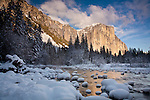 El Capitan reflected in a frozen Merced River in Yosemite National Park, CA, USA. El Capitan is a magnet for rock climbers, who may take several daya to reach the top.
