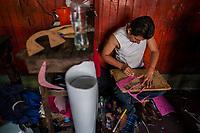 A Salvadoran shoemaker cuts an insole from a fiber insole sheet on the wooden desk in a shoe making workshop in San Salvador, El Salvador, 16 November 2016.