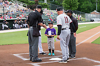 Kannapolis Intimidators guest manager Betty Altschuler delivers the line-up card to home plate umpire Mark Bass as Hickory Crawdads manager Spike Owen (11) and umpire  Darrell Roberts look on at Kannapolis Intimidators Stadium on April 22, 2017 in Kannapolis, North Carolina.  The Intimidators defeated the Crawdads 10-9 in 12 innings.  (Brian Westerholt/Four Seam Images)