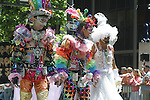 THREE PARADE MARCHERS GAILY DRESSED,HOLD HANDS as THEY MARCH <br />