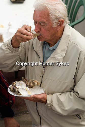 Whitstable Oyster Festival, Kent England 2007. Older man eating oysters.