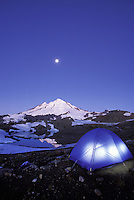 Tent glowing below Mt Baker and a full moon on a clear evening, North Cascades, Cascade Mountains, Washington