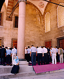 TURKEY, Istanbul, rear view of people praying at Sultan Ahmed mosque