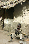 "A boy sits in front of a hut (""tukul"") in the Rumbek market, South Sudan."