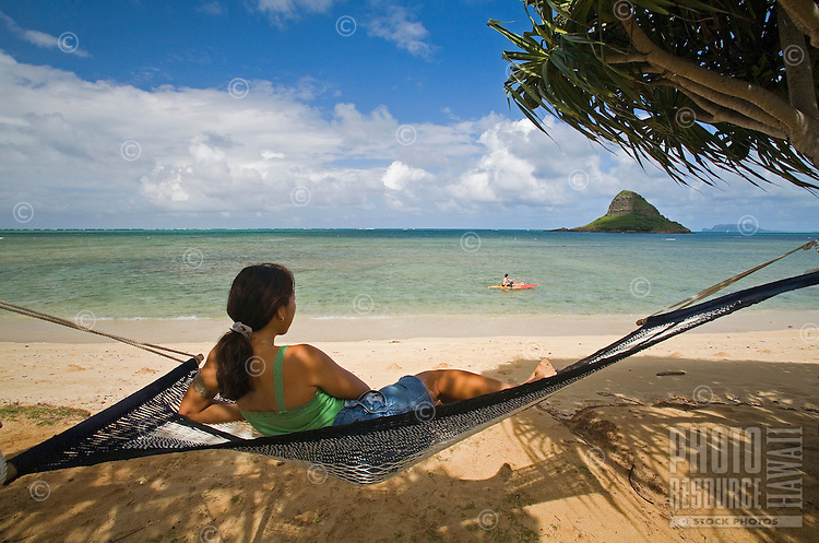 Young woman in hammock at beach, with Chinaman's Hat in background, Kualoa Regional Park, East Side of Oahu