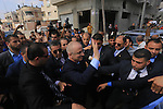Palestinian Prime Minister Rami Hamdallah waves to media upon his arrival to Gaza Strip in Beit Hanoun in the northern Gaza Strip on October 9, 2014. The Palestinian unity government which took the oath of office in June under technocrat prime minister Rami Hamdallah arrived to Gaza Strip on Thursday to convene the first fully meeting. Hamdallah said that the unity government will rebuild the bombed-out Gaza Strip following a seven-week Israeli offensive. Photo by Mohammed Asad
