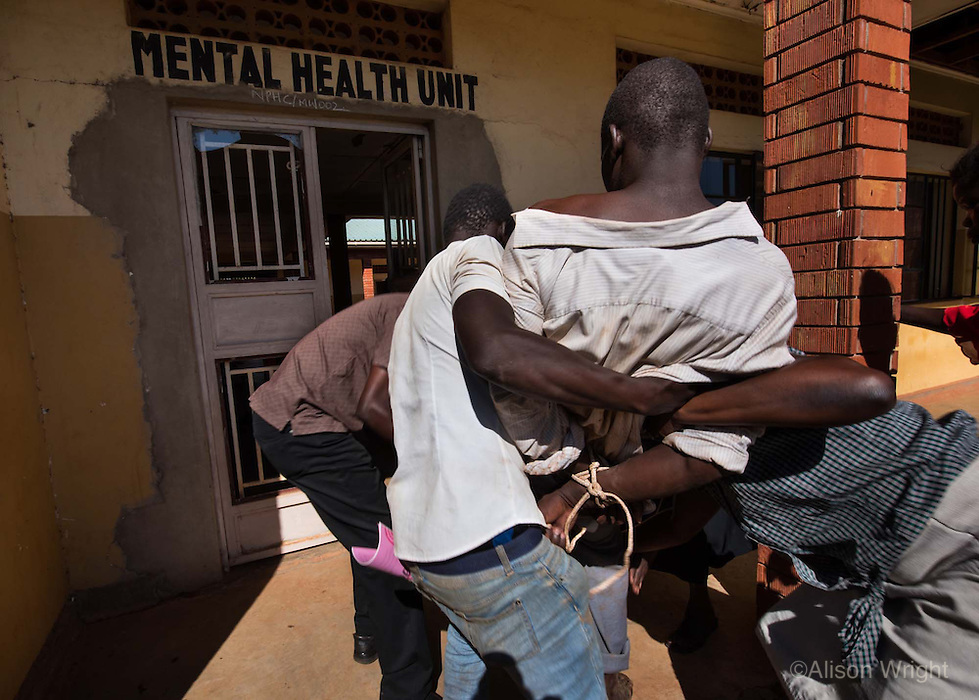 Africa, N. Uganda, Gulu. A mentally distressed man struggles as he's brought to the Gulu mental health clinic to be assessed. With so few resources to address mental health in Uganda the care usually falls to the family members. This man was brought to the local mental health clinic by his wife and brother to be evaluated and, as is often the case, he was so violent that he had to be sedated.