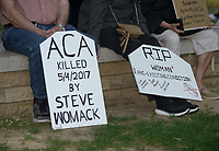 NWA Democrat-Gazette/BEN GOFF @NWABENGOFF<br /> Participants hold signs Sunday, May 7, 2017, during a 'Die-In for ACA' hosted by Ozark Indivisible on the Bentonville square. The group marched around the square and lay down in a 'die-in,' with many holding tombstone-shaped signs carrying personal messages about how healthcare costs and losing coverage for pre-existing conditions could lead to their premature death. The event comes after the U.S. House of Representatives approved legislation Thursday to largely repeal and replace the Affordable Care Act.