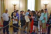 Tourists use their cell phone cameras to take photos during their tours of the White House in Washington, D.C. on Wednesday, July 1, 2015. The White House announced it lifted its longstanding ban on photos during public tours.  This ban has been in place for over 40 years.  Effective today, guests are now welcome to take photos during their tours of the White House. An unidentified person holds a sign with the former policy.  <br /> Credit: Ron Sachs / Pool via CNP